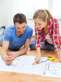 Smiling couple looking at blueprint at home. Repair, building, renovation and home concept - smiling couple looking at blueprint at home stock photos