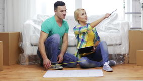 Smiling couple looking at blueprint in new home. Moving, home and couple concept - smiling couple relaxing on sofa and looking at blueprint in new home stock footage