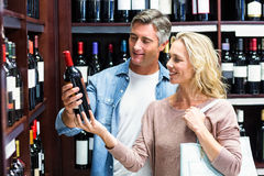 Smiling couple looking at bottle of wine Stock Photography