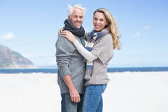 Smiling couple looking at camera on the beach in warm clothing Stock Image