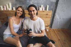 Smiling couple looking into camera while sitting on a bed. Man and women looking into camera while men holding his own photo camera Stock Image
