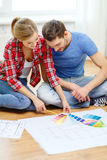 Smiling couple looking at color samples at home. Repair, interior design, building, renovation and home concept - smiling couple looking at color samples at home royalty free stock photography