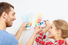 Smiling couple looking at color samples at home. Repair, interior design, building, renovation and home concept - smiling couple looking at color samples at home royalty free stock photos
