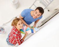 Smiling couple looking at color samples at home. Repair, interior design, building, renovation and home concept - smiling couple looking at color samples at home royalty free stock photo