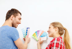 Smiling couple looking at color samples at home. Repair, interior design, building, renovation and home concept - smiling couple looking at color samples at home stock photos