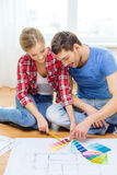 Smiling couple looking at color samples at home. Repair, interior design, building, renovation and home concept - smiling couple looking at color samples at home stock photo