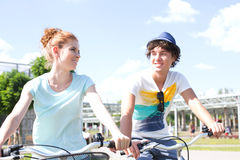 Smiling couple looking at each other while cycling in city Royalty Free Stock Images