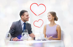 Smiling couple looking at each other at restaurant Stock Image