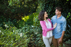 Smiling couple looking face to face in garden. On a sunny day Royalty Free Stock Photo