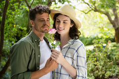 Smiling couple looking at flower in garden. Couple smelling flower in garden on a sunny day royalty free stock image