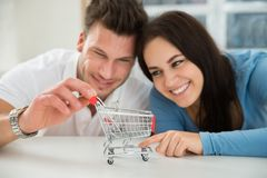 Smiling couple looking at miniature shopping cart Royalty Free Stock Photography