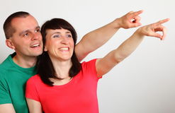 Smiling couple looking and pointing into distance Stock Photo