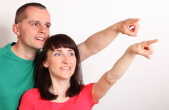 Smiling couple looking and pointing into distance Royalty Free Stock Photography