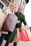 Smiling couple looking into shopping bags on the street Stock Photos