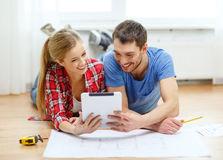 Smiling couple looking at tablet pc at home. Repair, building, renovation and home concept - smiling couple looking at tablet pc at home stock images