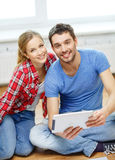 Smiling couple looking at tablet pc at home. Repair, building, renovation and home concept - smiling couple looking at tablet pc at home Stock Photo