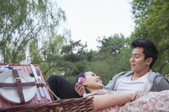 Smiling couple in love having a picnic in the park, lying down on the blanket with picnic basket open Royalty Free Stock Image