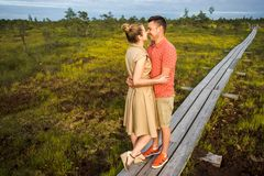 smiling couple in love hugging each other on wooden bridge with green plants stock photos