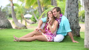 Smiling Couple In Love with Lei, Sitting And Hugging under palm tree. Portrait of a happy and romantic couple wearing flower Lei on beach Oahu Hawaii stock video footage