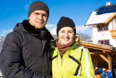 Smiling couple in love posing against winter ski resort Stock Image
