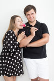 Smiling couple in love posing with red lollipop Stock Photo