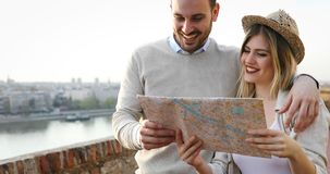 Smiling couple in love traveling with a map outdoors Royalty Free Stock Photography