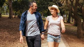 Smiling couple in love walking in the park. Beautiful couple walking through a park holding hands and looking at each other. Smiling men and women in love royalty free stock images