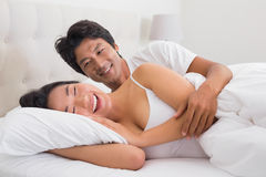 Smiling couple lying in bed royalty free stock image