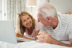 Smiling couple lying on bed and using laptop Stock Images