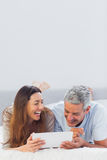 Smiling couple lying on bed using their tablet pc Stock Photography