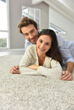 Smiling couple lying on the carpet Royalty Free Stock Photos