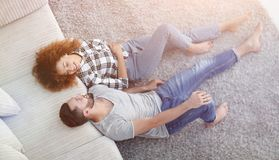Smiling couple lying on a carpet in a new apartment. Top view of a smiling couple lying on a carpet in a new apartment royalty free stock photos