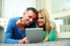 Smiling couple lying on the carpet Royalty Free Stock Photography