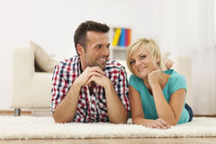 Smiling couple lying down on carpet Royalty Free Stock Photography