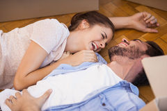 Smiling couple lying on the floor Stock Images