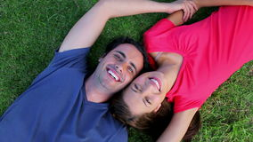 Smiling couple lying on the grass while enjoying the nature Stock Photography