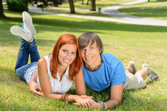 Smiling couple lying in park first love Royalty Free Stock Image