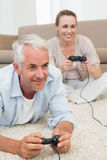 Smiling couple lying on rug playing video games Royalty Free Stock Photos