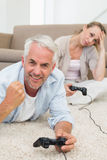 Smiling couple lying on rug playing video games Royalty Free Stock Photography