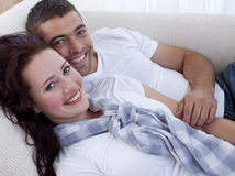 Smiling couple lying on sofa Royalty Free Stock Image