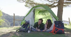 Smiling couple lying in tent and talking stock video footage