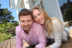 Smiling couple lying on wooden terrace Royalty Free Stock Photography