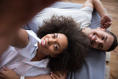 Smiling couple making selfie while lying in bed Stock Photos