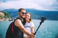Smiling couple making selfie photo at Lake Garda, Italy. Tourist, couple of lovers making selfie photo on motion camera at Lake Garda, Italy, Europe. Holidays stock photos