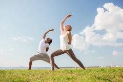 Smiling couple making yoga exercises outdoors Stock Images