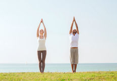 Smiling couple making yoga exercises outdoors Royalty Free Stock Image