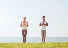 Smiling couple making yoga exercises outdoors Stock Image