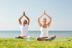 Smiling couple making yoga exercises outdoors Stock Images