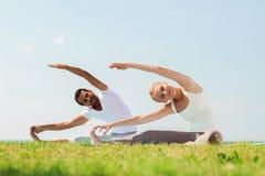 Smiling couple making yoga exercises outdoors Stock Photos