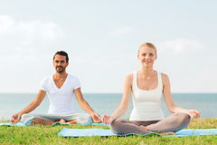 Smiling couple making yoga exercises outdoors Stock Photography
